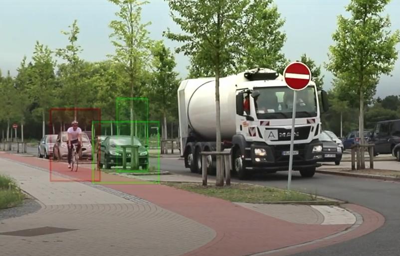 Fahrradfahrer auf Radweg hinter parkenden Autos